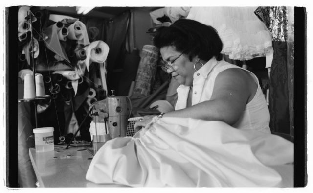 "Milagros ""Millie"" Cueto sewing gown with sewing machine."