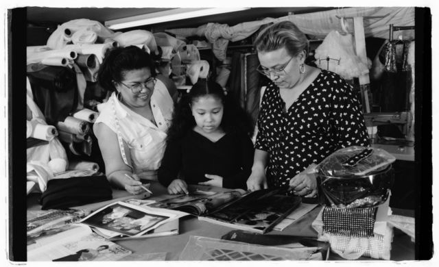 "Milagros ""Millie"" Cueto, unidentified girl, and Elsa Mantilla examine photos and sketches of dress."