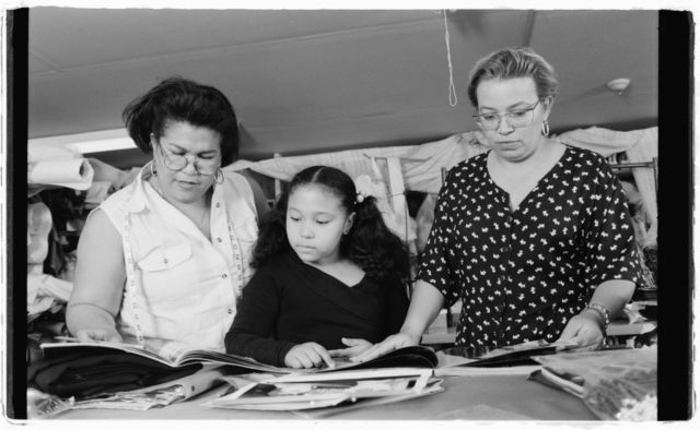 """Milagros """"Millie"""" Cueto, unidentified girl, and Elsa Mantilla examine photos and sketches of dress."""