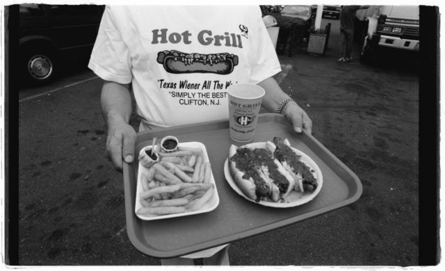 Nick Doris stands in front of The Hot Grill holding tray of food; he is wearing a Hot Grill t-shirt.