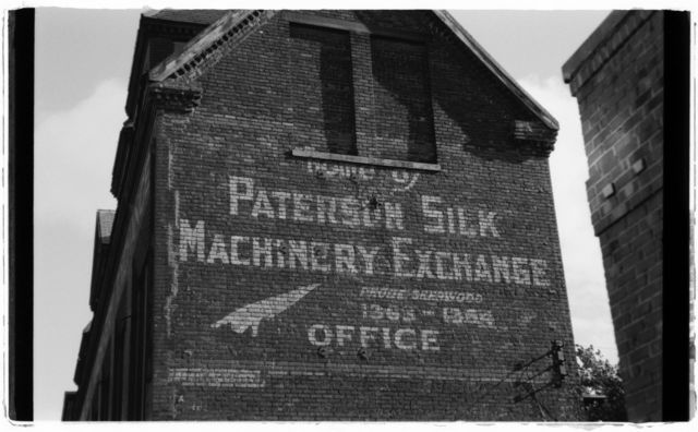 "Old advertising painted on exterior wall of brick building on Spruce Street; it reads:  ""Home of Paterson Silk Machinery Exchange."""