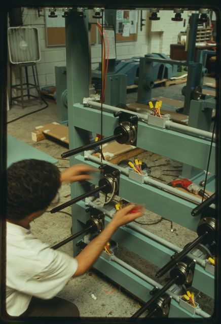 Omar Abukharma installing and testing tension bars on a horizontal pay-off machine.
