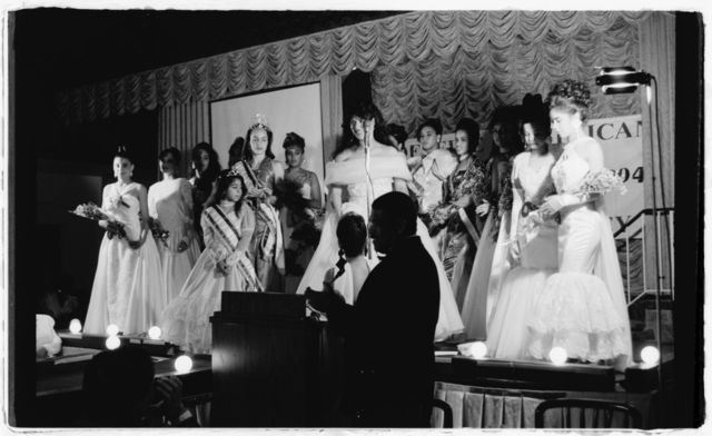 Pageant contestants on stage with Elsa Mantilla and others.
