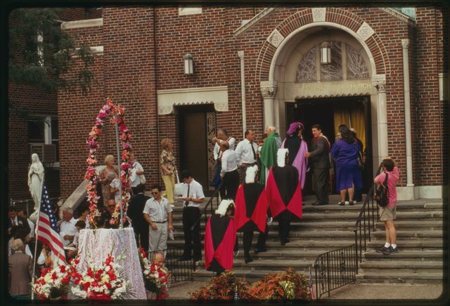 People stand on front steps of church as members of Knights of Columbus walk up the steps.