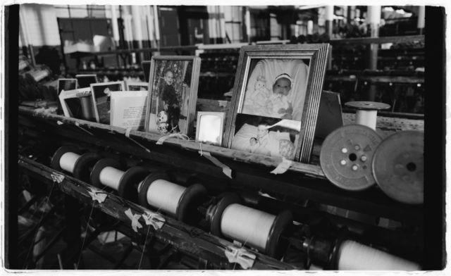 Photos of Cindy's children and other personal items on rail above winding machine at her work station.