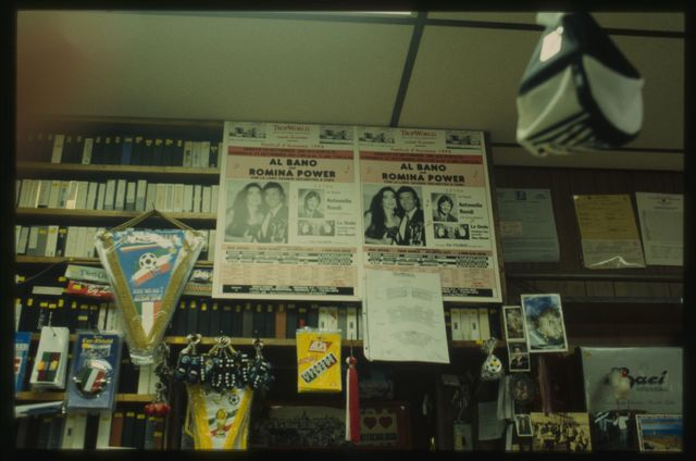 Posters advertising an Italian music performance, behind which are rows of Italian movies in video format.