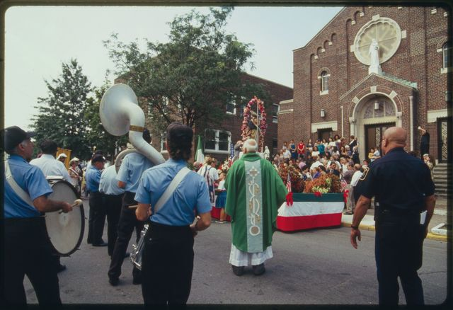 Priest and band members stand in Beech Street (opposite St. Anthony's Church) waiting for procession to resume after the mass; part of crowd and front of church are visible.