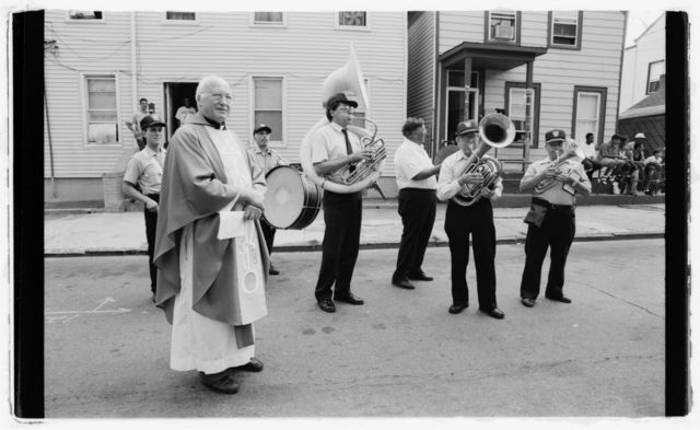 Priest and band members stand in street waiting for procession to resume.