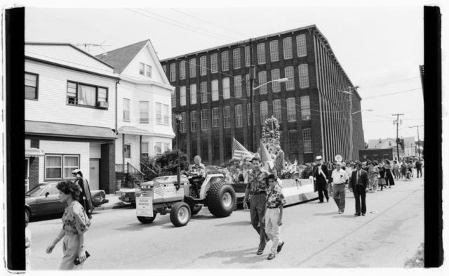 Procession passes old brick textile-manufacturing building on 21st Avenue.
