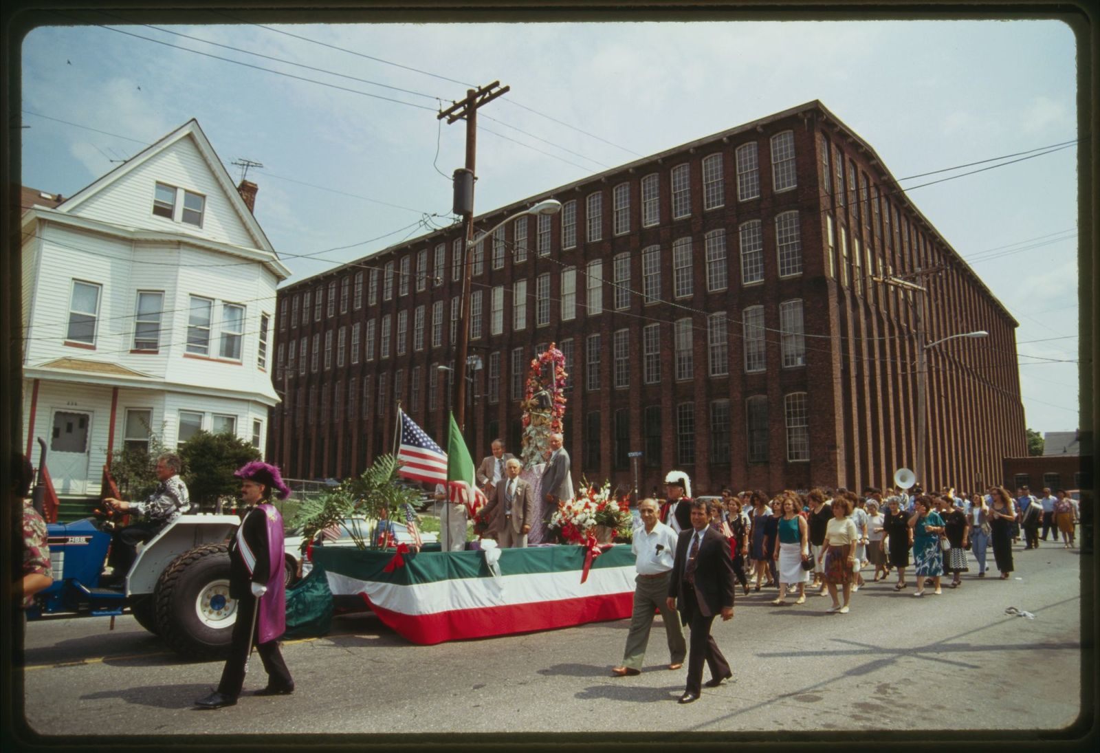Procession travels down 21st Avenue; brick factory building is in the background.