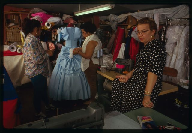 """Proprietor Elsa Mantilla (in dotted dress) with seamstresses Aurora Goicoechea (in long-sleeved blouse) and Milagros """"Millie"""" Cueto; blue gown is being worked on in the background."""