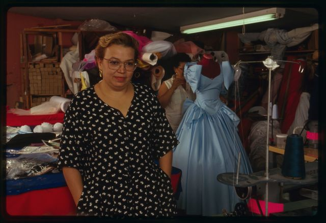 "Proprietor Elsa Mantilla (in dotted dress) with seamstresses Aurora Goicoechea (in long-sleeved blouse) and Milagros ""Millie"" Cueto; blue gown is being worked on in the background."
