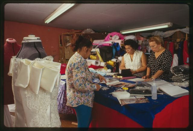 "Proprietor Elsa Mantilla (in dotted dress) with seamstresses Aurora Goicoechea (in long-sleeve blouse) and Milagros ""Millie"" Cueto."