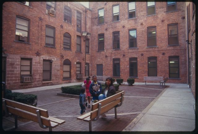 Resident of Essex Mill Apartments in courtyard with her children; the woman is Té Jai Petersen, a former singer and actress turned writer; artists received rent reductions from Essex Mill Apartments; the building is at 24 Mill Street.