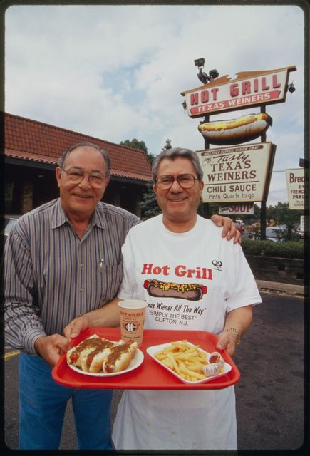 """Restaurant co-owner Nick Doris (right) with friend Bill Betts (another hot Texas Wiener restaurateur) stand in front of The Hot Grill  holding a tray with three hot Texas wieners """"all the way,"""" an order of French fries, and a soft drink."""