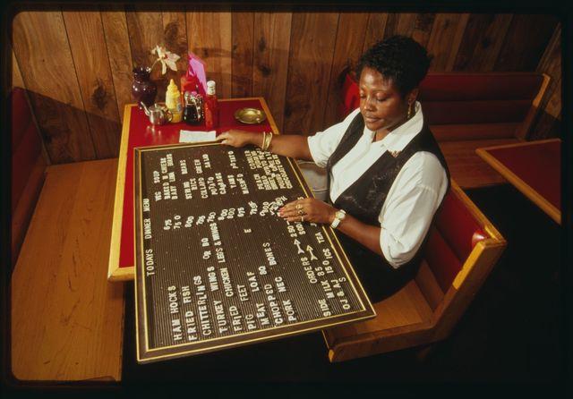 Restaurant worker Gladys Prior arranges menu board.