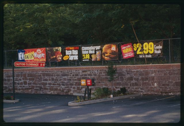 Signs on fence around Burger King parking lot, on site on former mill building, on Spruce Street.