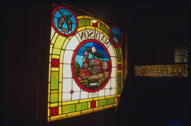 Stained-glass window at Madison Four Diner, at the corner of Madison & Getty Avenues; the window depicts Colt pistols, a Rogers locomotive, and the bridge over the Great Falls on the Passaic River.