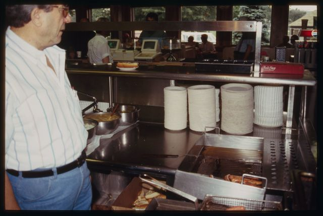 The Hot Grill's preparation line for Hot Texas Wieners, showing equipment, work surfaces, containers of toppings, and frying area.