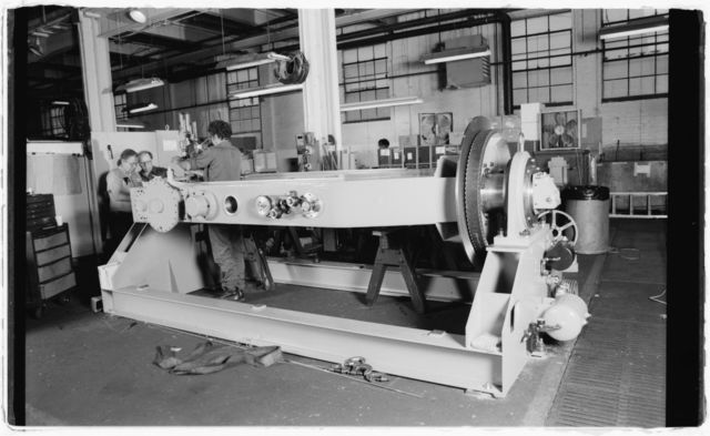 Three workers with large machine.