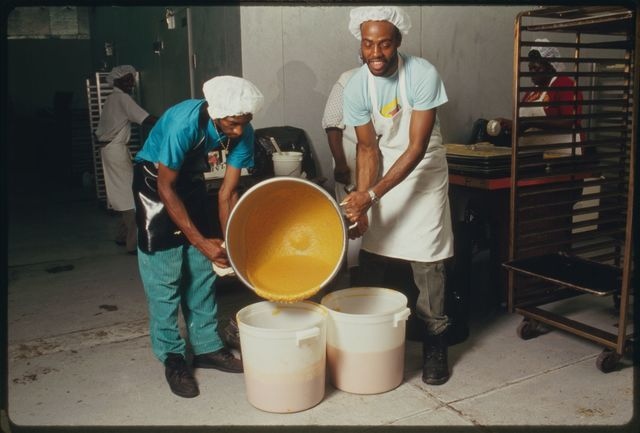 Two workers pour sweet potato batter from mixing bowl into plastic buckets.