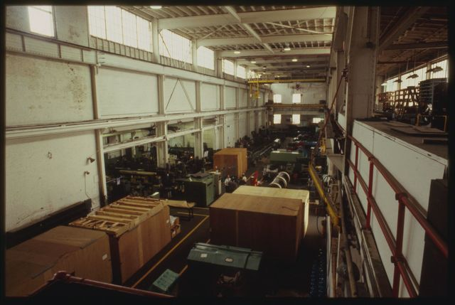 View of machine shop from catwalk above; in this view you are looking south with the crane in the distance, the crates in the foreground contain machines either completed or awaiting repair.
