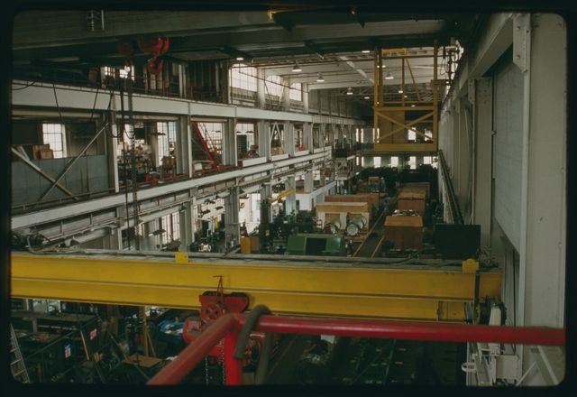 View of machine shop from south end with crane in foreground.