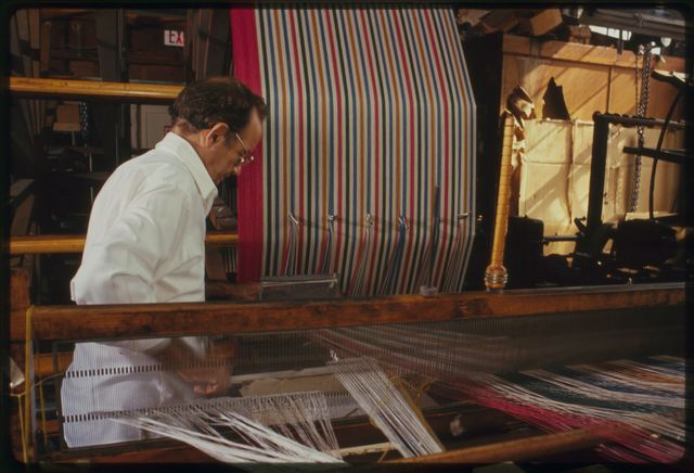 """Warper Al Zarky """"making a warp""""; the large circular piece of equipment is called a """"warping frame,"""" it was manufactured in Paterson by the Sipp Machine Company."""