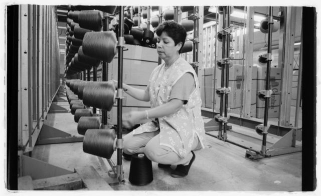 Woman (Theresa) arranging spools of thread near the warping area.