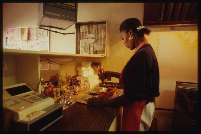Worker prepares sandwiches.