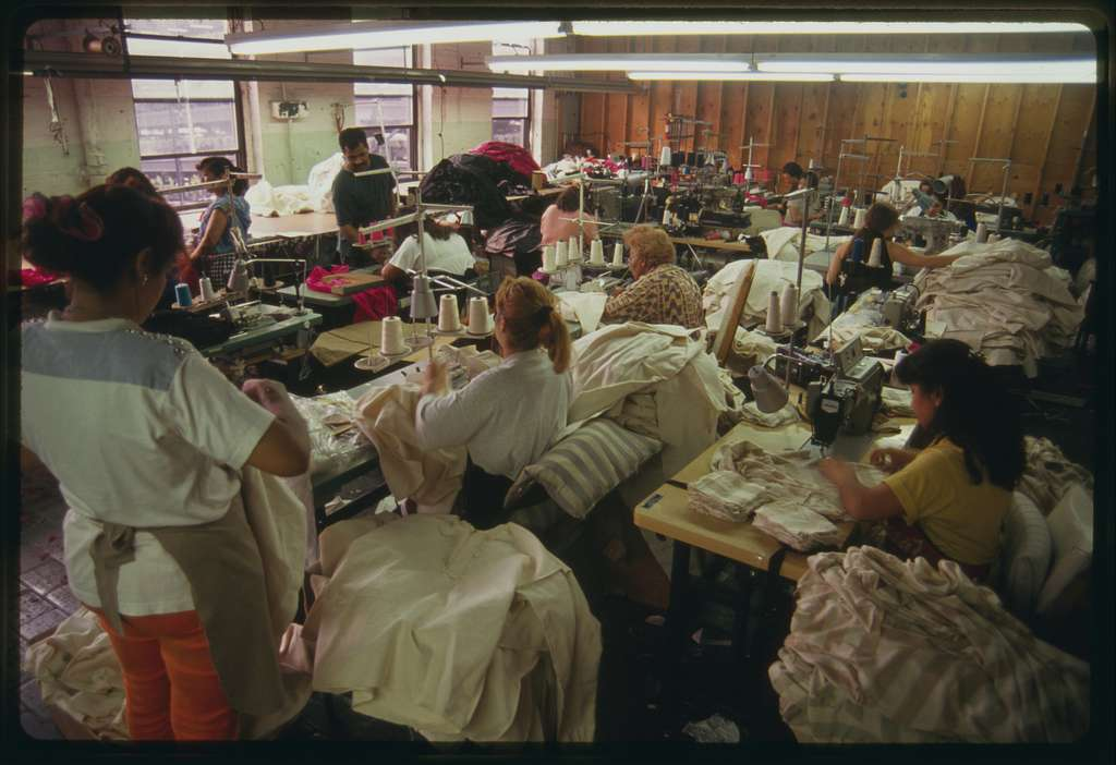 Workers at work, most are sitting behind sewing machines
