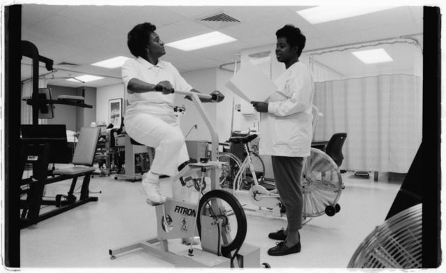 Workers in physical therapy unit, 1st floor:  Roxie Jackson, physical therapist assistant (left), and Shirley Nealy, physical therapist aide (on exercise bike).