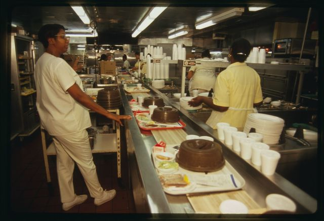 Workers on assembly line in hospital's kitchen; they are making up meals to be delivered to patients.