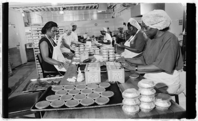 Workers wrapping cooked pies with plastic wrap.