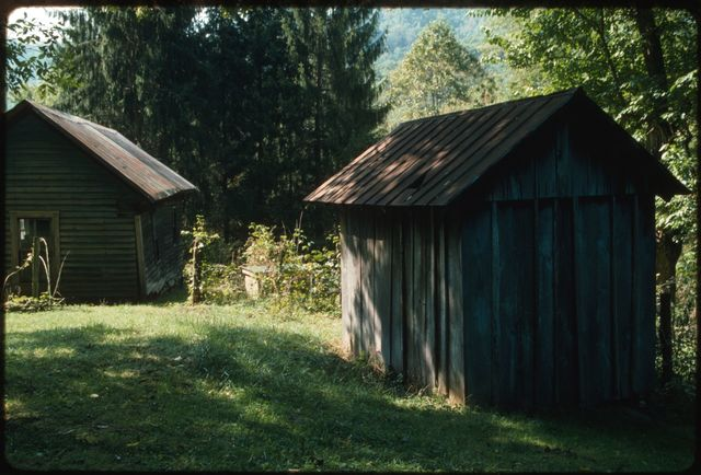 Outbuildings on the Dickens property:  rear of chestnut smoke house with former family residence in the background, made of poplar