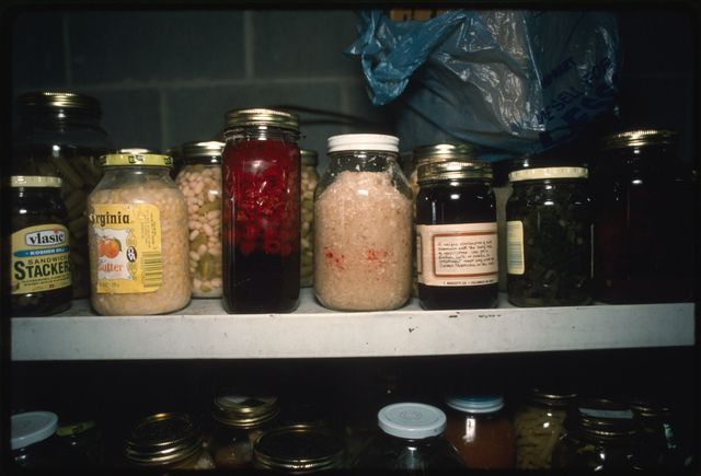 A shelf of canned goods in Edna Turner's cellar, including corn, beans, slaw, wild berries, blackberry juice, and ramps