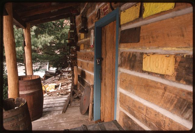 Exterior of log house built by Woody Boggs.  Front porch with old saw and license plates used for decorative purposes I.