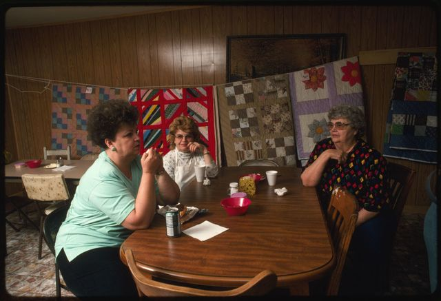Foreground (L-R):  Judy Griffey, Shirley Tyler, and Edna Turner at the Drews Creek Church ramp supper.  Quilts hanging in the background are for sale.