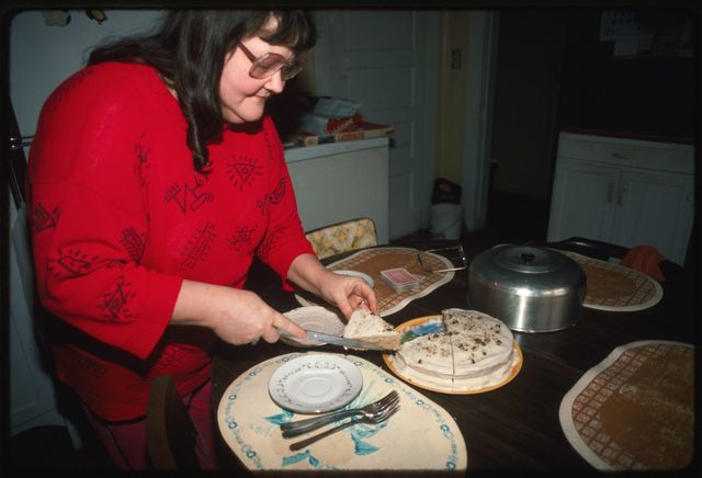 Glenna Bailey (Right) serving a slice of her black walnut cake to Mary Hufford and Dave Bailey