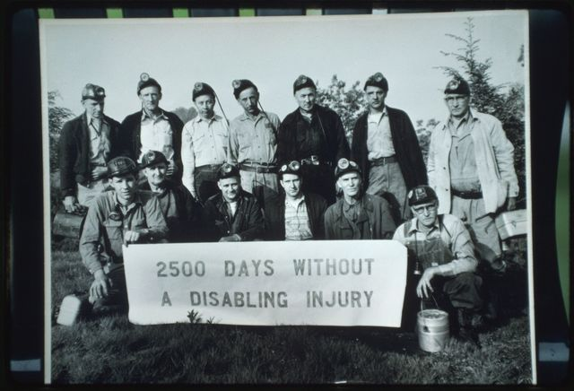 "Historic photo, property of Cody Dickens:  undated photograph of Montcoal #1, Armco Steel Corp, 9 West day-shift miners posed behind a safety banner that reads ""2500 Days Without a Disabling Injury"""