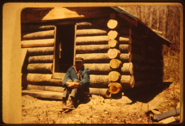 Hobart Clay, of Shumate's Branch, in front of log cabin built by Woody Boggs