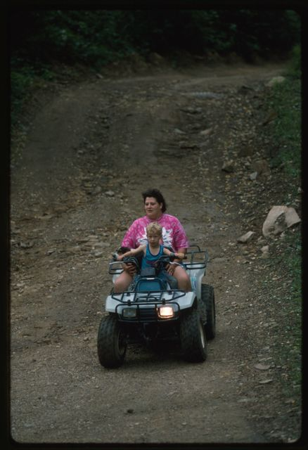 Unidentified woman and child riding four-wheeler