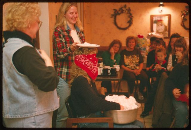 Crystal Pettry and Stacy Edmunds assist in a baby shower game which requires the blindfolded participant to scoop cotton balls from a bowl in her lap onto a plate on her head