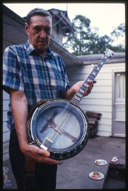 Dave Bailey holding Russell Cox's banjo with crucifix painted on back