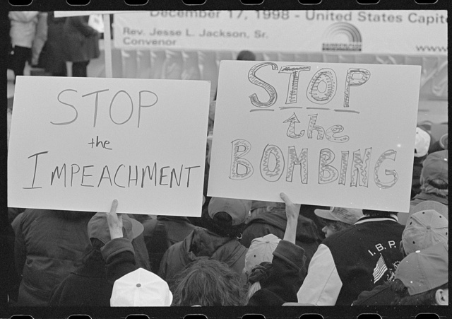 "[Demonstrators hold signs reading ""Stop the impeachment"" and ""Stop the bombing"" at an outdoor rally sponsored by the Rainbow PUSH Coalition protesting the impeachment of President Bill Clinton]"