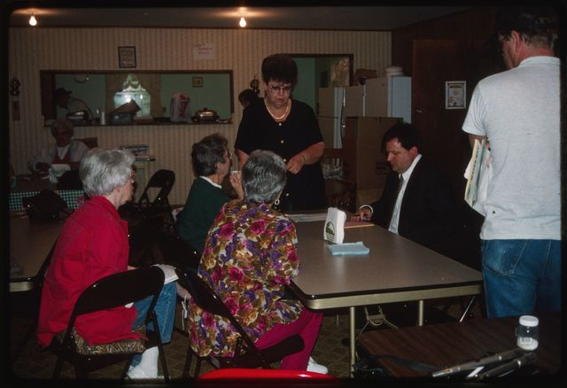 Judy Griffy (standing) with Bob Kiss (seated, in suit)