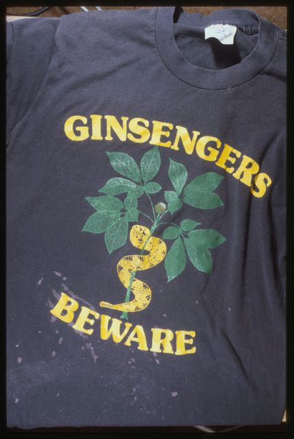 """T-Shirt:  """"Ginsengers Beware.""""  Graphic depicts ginseng plant with rattlesnake wrapped around the stalk."""