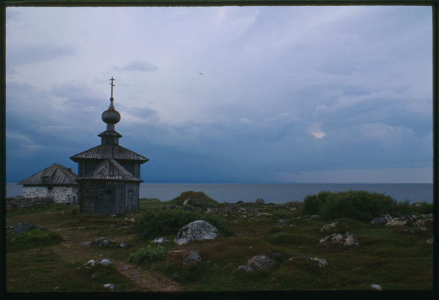 Church of St. Andrew (1702), east view, with stone dwelling (mid 16th century), and White Sea in background, Bol'shoi Zaiatskii Island, Russia