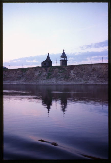 """Log Chapel of Basil the Blessed and belltower (1823), west view taken from Dvina River on sidewheeler """"N.V. Gogol"""", Chukhchena, Russia"""