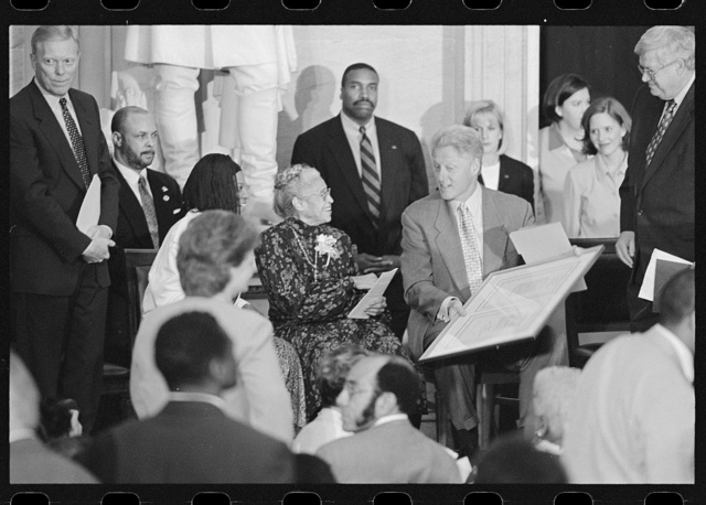 [Rosa Parks at her Congressional Gold Medal ceremony seated with assistant Elaine Steele (left); President Bill Clinton, Representatives Dennis Hastert, Dick Gephardt and others stand behind them]